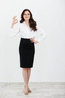 Portrait of business woman holding ok finger sign isolated on plain white background