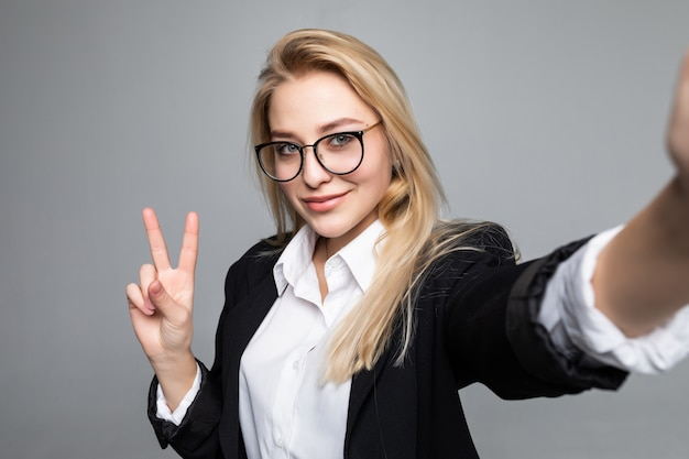 Portrait of business woman making selfie using smart phone and internet, gesturing peace symbol, having video call online over grey wall