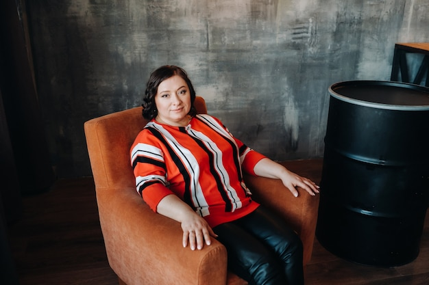 Portrait of a business woman in a striped jacket sitting on a sofa in the interior.