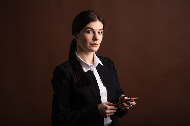 Portrait of a business woman who uses her smartphone in the studio on a brown background
