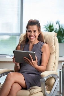 Portrait of business woman working on tablet computer in her office chair