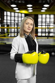 Portrait of a business woman in yellow boxing gloves on the background of a boxing ring