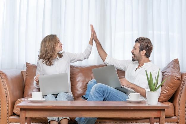 肖像画のビジネスマンとビジネスウーマンは、ホームオフィスでコンピューターのラップトップを使用してhi5を与えます