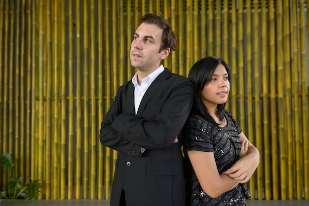 Portrait of businessman and asian businesswoman as multi ethnic couple together against bamboo wall outdoors