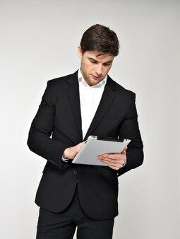 Ritratto di uomo d'affari in abito nero con pad. comunicazione di concetto.