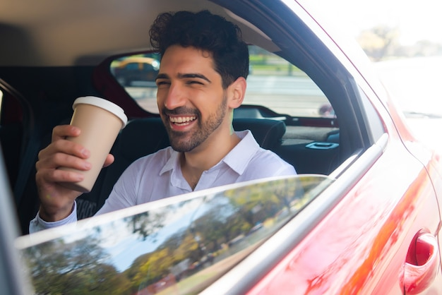 Portrait of businessman drinking coffee on his way to work in car