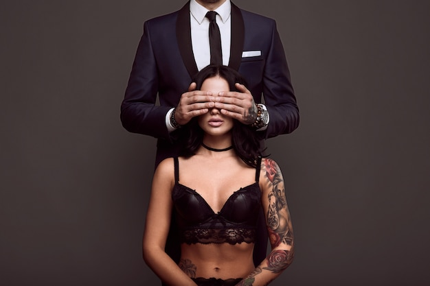 Portrait of a businessman in elegant suit cover eyes of sexy woman with a tattoo in lingerie