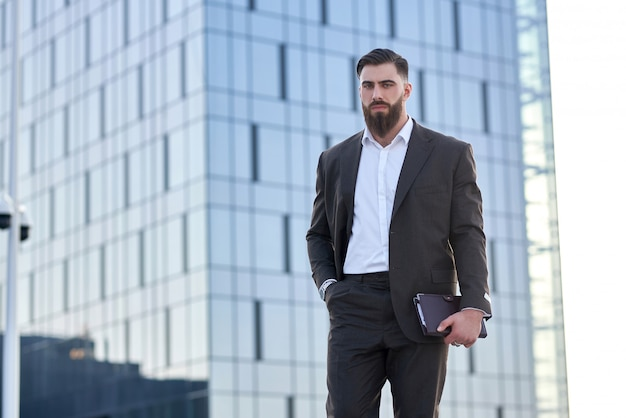 Portrait of a businessman in front of corporate buildings