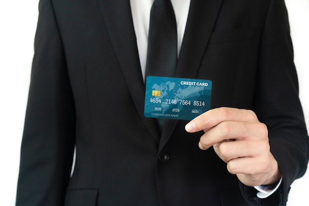 Portrait of businessman holding a credit card showing front view to the camera in close up view.