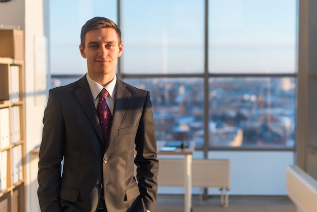 Portrait of businessman, looking at camera, standing in office.