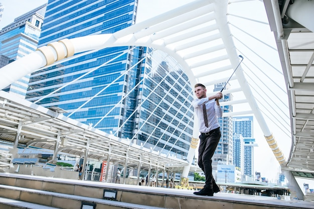 Portrait of businessman playing golf with cityscape on the background. business leisure concept.