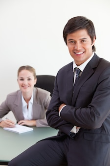 Portrait of a businessman posing while his colleague is working