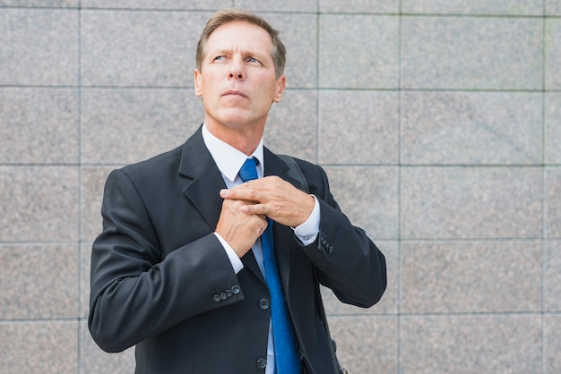 Portrait of a businessman standing in front of tiled wall