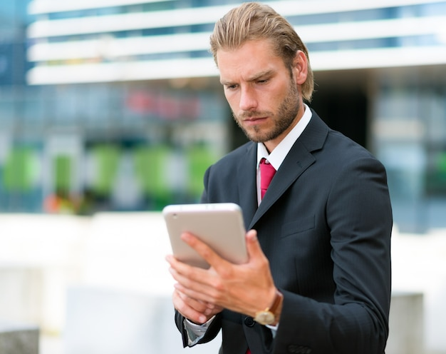 Portrait of a businessman using his tablet