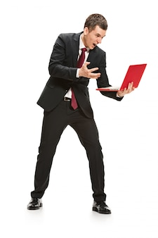 Portrait of businessman with laptop on white wall