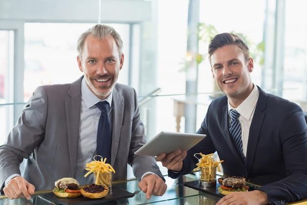 Portrait of businessmen using digital tablet in restaurant