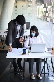 Portrait of businesspeople wearing protective mask co working in modern office.