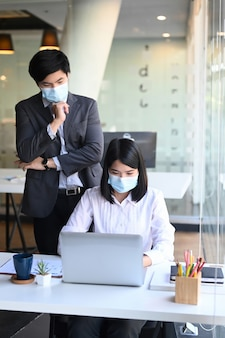 Portrait businesspeople wearing protective mask working together in modern office.