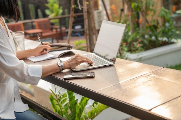 Ritratto di imprenditrice in un caffè utilizzando un computer portatile