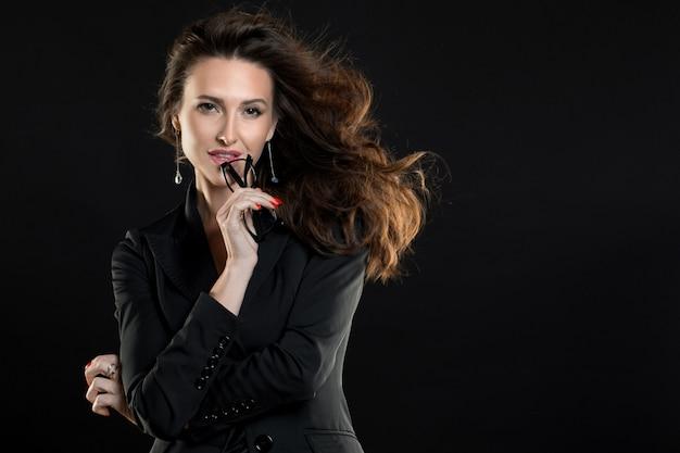 Portrait of a businesswoman over dark background.