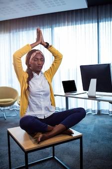 Portrait of businesswoman doing yoga