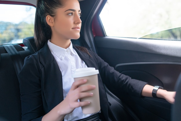 Portrait of businesswoman drinking coffee on his way to work in car