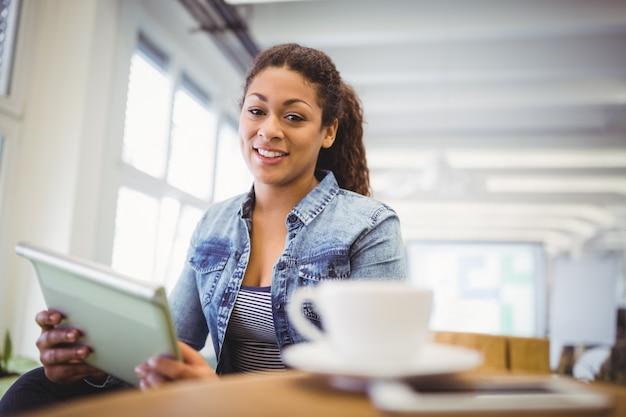 Portrait of businesswoman holding digital tablet in office