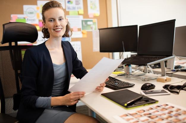 Portrait of businesswoman holding document at desk