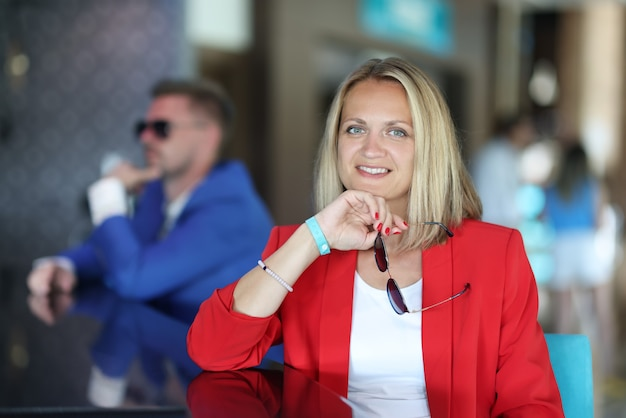 Portrait of businesswoman in red jacket at bar