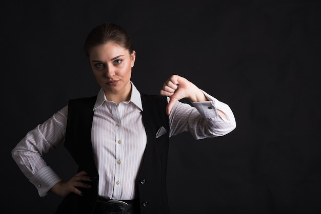 Portrait of a businesswoman showing a thumb down gesture