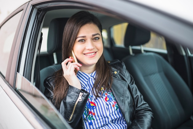 Portrait of a businesswoman sitting in car talking on cellphone