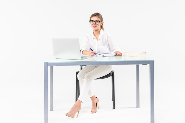 Portrait of a businesswoman sitting at a desk with a laptop isolated on white background