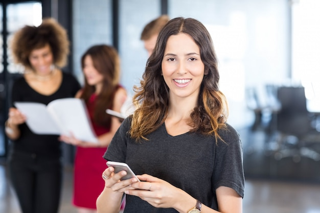 Portrait of businesswoman text messaging on smartphone while her colleagues standing behind her in office