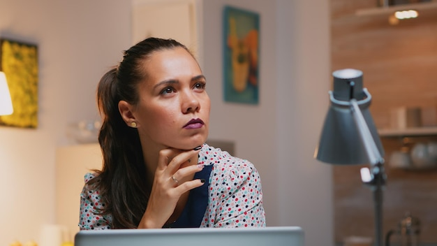 Portrait of businesswoman thinking of email answer working at home sitting on kitchen desk. close up of busy employee using modern technology network wireless doing overtime reading writing, searching