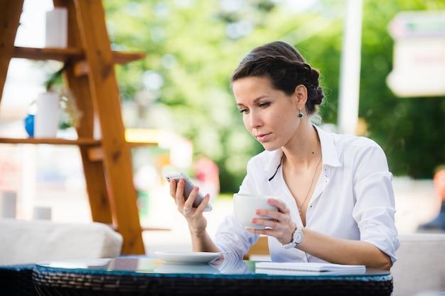 Portrait of a businesswoman using smart phone in sidewalk cafe.