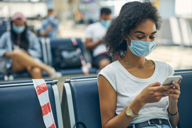Portrait of businesswoman wearing face mask during virus epidemic while sitting in departure lounge at the airport