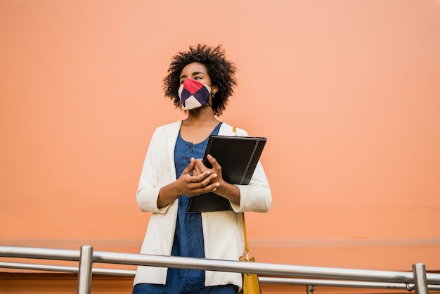 Portrait of businesswoman wearing protective mask and holding a clipboard while standing outdoors