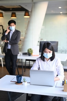 Portrait of businesswoman wearing protective mask working on laptop and her colleague talking on mobile phone in background.
