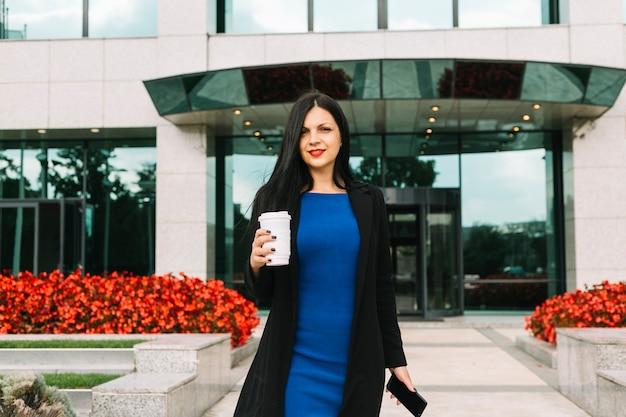 Ritratto di una donna d'affari con cellulare e tazza di smaltimento