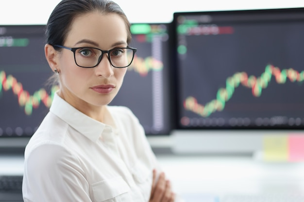 Portrait of businesswoman with glasses on background of electronic stock market analytics