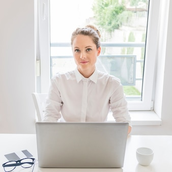 Portrait of businesswoman with laptop sitting in front of window