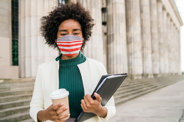 Portrait of businesswoman with protective mask holding a cup of coffee and clipboard