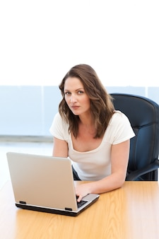 Portrait of a businesswoman working on laptop at a table