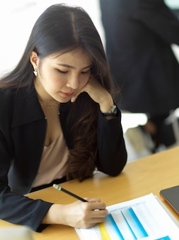 Portrait of businesswoman writing on paperwork while analysing on business paperwork in office room