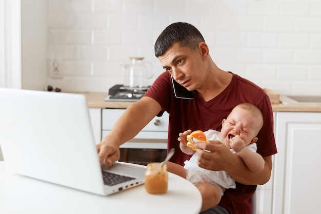 Portrait of busy brunette male freelancer wearing maroon casual style t shirt sitting at table in kitchen with his infant daughter and talking via cell phone with customer.