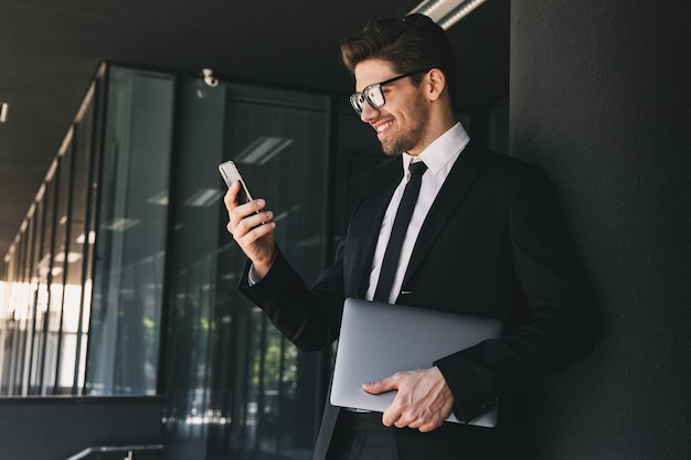 Portrait of busy businessman dressed in formal suit standing outside glass building with laptop, and using mobile phone