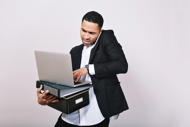 Portrait busy hard-working astonished businessman with office folders, laptop talking on phone. office worker, career, misunderstanding, smart handsome man.
