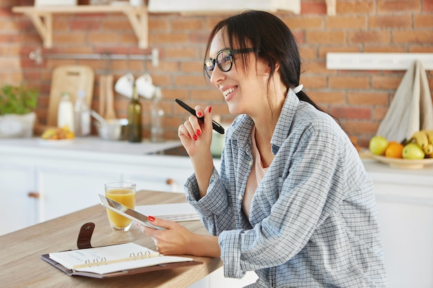 Portrait of busy woman creates project, searches information in tablet, writes notes at notebook