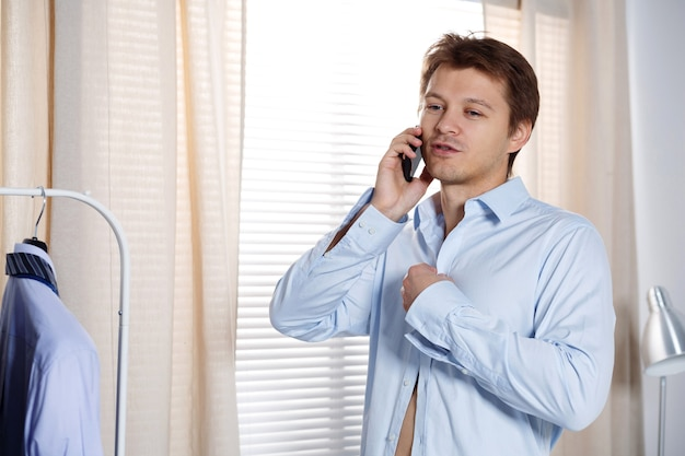 Portrait of busy young man putting on his shirt and talking on phone. broker, agent or sales manager hasten to work. hurry to important meeting or office. support concept