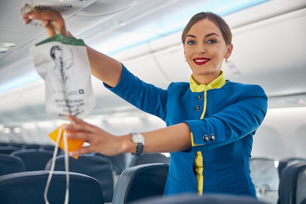 Portrait of cabin crew holding up the oxygen mask during the safety demonstration on board commercial international airlines